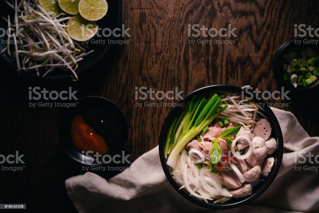 Traditional Vietnamese soup Pho bo with herbs, meat, rice noodles, broth. Pho bo in bowl with chopsticks. Top view. Asian soup Pho bo on wooden table background. Vietnamese soup stock photo