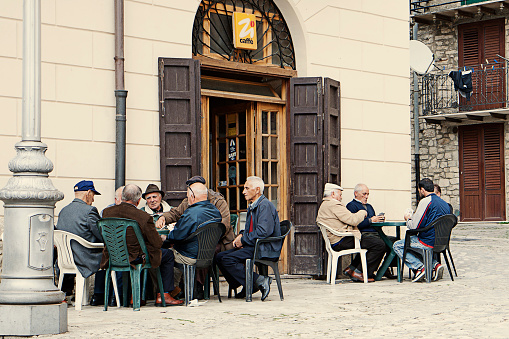 Traditional view of Italian old men sitting in an outdoor cafe, playing cards, drinking coffee and chatting.