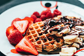 Traditional waffles and strawberries, with bananas and chocolate
