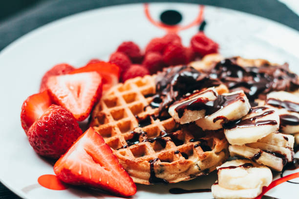 Traditional waffles and strawberries Traditional waffles and strawberries, with bananas and chocolate waffle stock pictures, royalty-free photos & images