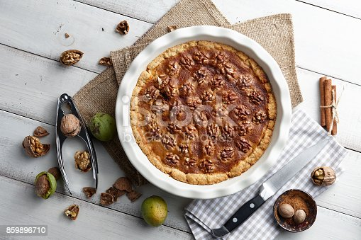 istock Traditional walnut pie with ingredients on white table 859896710