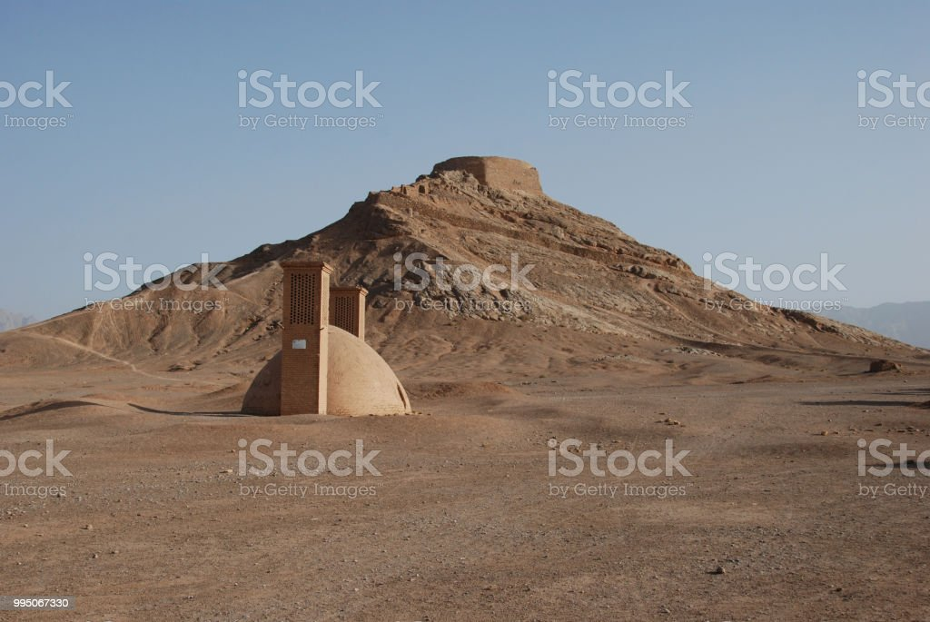 Traditional water well with Zoroastrian tower of in the backgorund stock photo