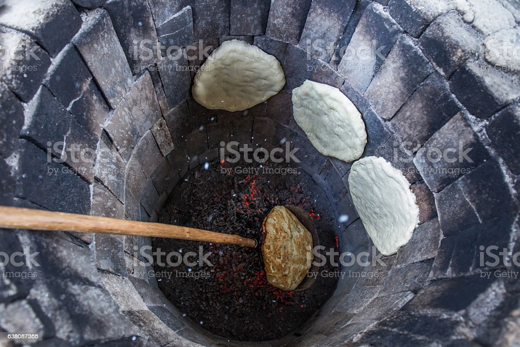 Traditional way of baking bread in the tandoor in Armeina stock photo