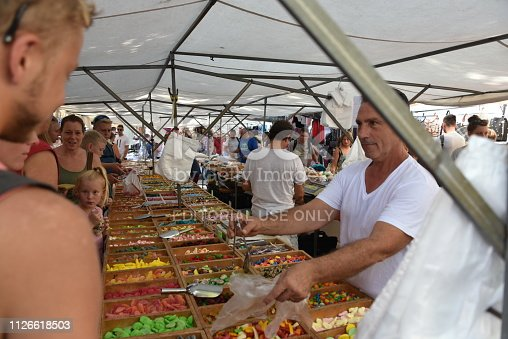 Alcudia, Majorca, Spain - August 19, 2018: man is selling sweets at the traditional weekly market in Alcudia, Spain