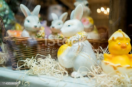 traditional white easter bunny inside bakery shop window with straw, eggs and poult in traditional set up
