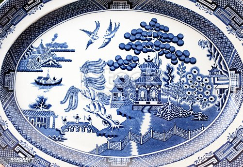An antique blue and white oval platter with the classic traditional willow pattern.