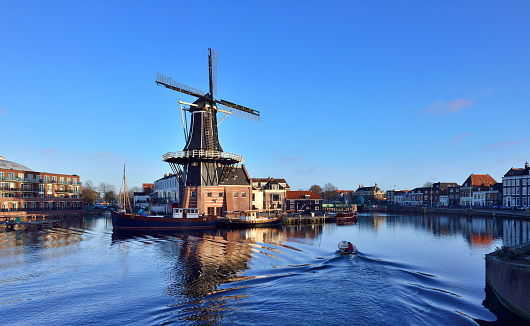 Traditional windmill at prinsengracht canal in blue sky at sunset, Amsterdam, Netherlands.