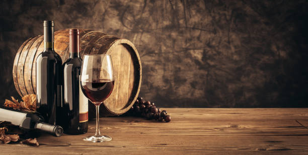 Traditional winemaking and wine tasting Wine glass, wooden barrel and collection of excellent red wine bottles in the cellar: traditional winemaking and wine tasting concept cellar stock pictures, royalty-free photos & images