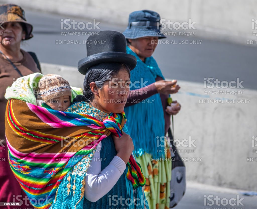 Traditional Woman (Cholita) in Typical Clothes with baby on her back during 1st of May Labor Day Parade - La Paz, Bolivia stock photo