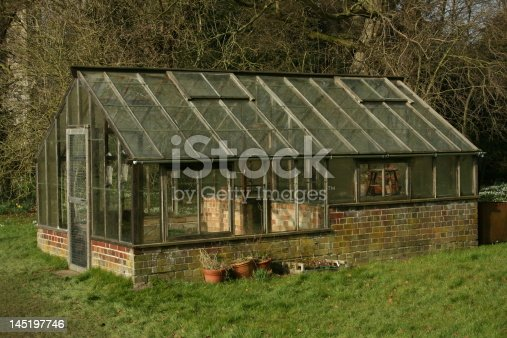 A Large, traditional Wood and Brick Greenhouse in the Winter with lawn in front and trees behind.