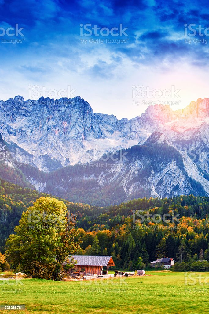 Traditional Wooden Alpine Chalet Autumn at Sunset and Snowy Mountains stock photo