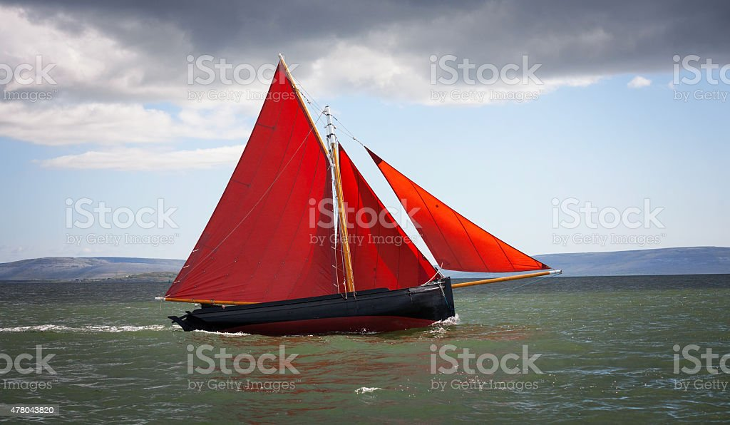 Traditional wooden boat with read sail. stock photo