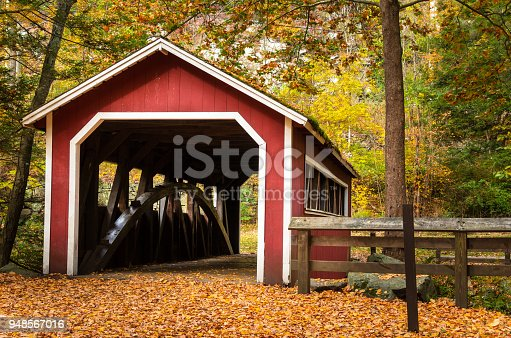 Old Red Covered Bridge in a Forest in Fall. The Path Leading to the Bridge is Completely Covered in Fallen Leaves. Southford Falls State Park, CT