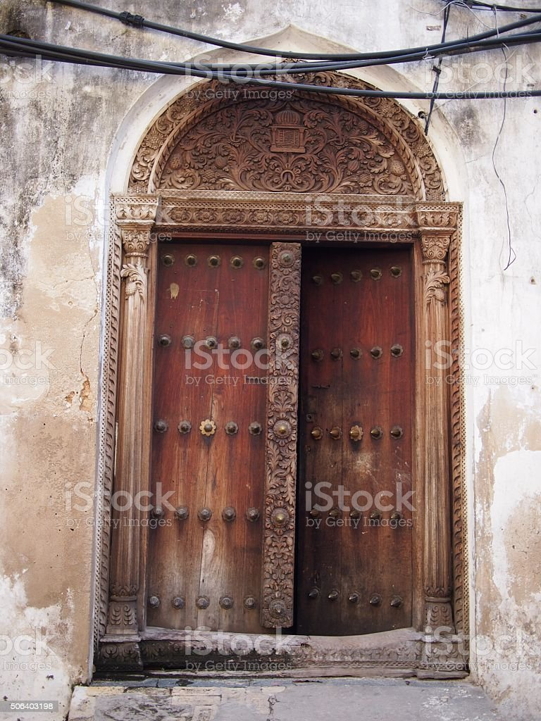 Traditional wooden door with curved arch in Zanzibar stock photo