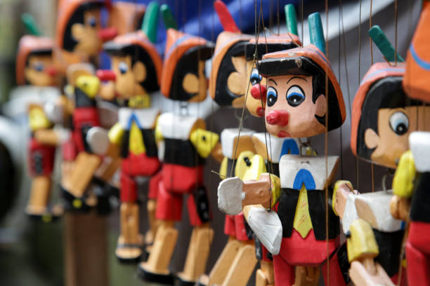 Traditional wooden Pinocchio toy on the market Traditional wooden Pinocchio toy on the market pinocchio stock pictures, royalty-free photos & images