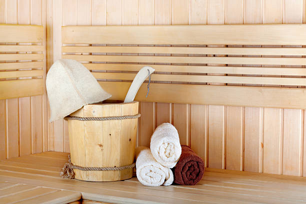 traditionelle hölzerne sauna zur entspannung mit eimer mit wasser - sauna textilien stock-fotos und bilder