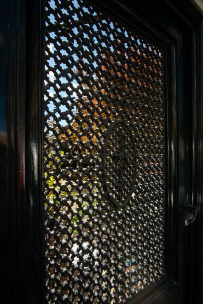 traditionele smeedijzeren kunstwerk in een deur, gemaakt door een zwarte smith. details van een nederlandse stad met traditionele houten vintage vakwerkhuis, cuktural, vakmanschap, erfgoed - beemster stockfoto's en -beelden