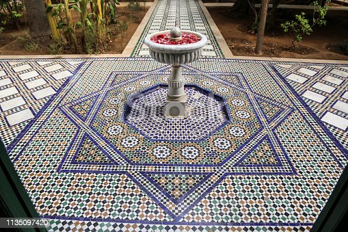 Traditional yard in a riad in Morocco with mosaic tiles floor and a fountain with petals.