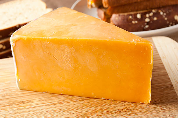 Traditional Yellow Cheddar Cheese Traditional Yellow Cheddar Cheese on a background cheddar cheese stock pictures, royalty-free photos & images