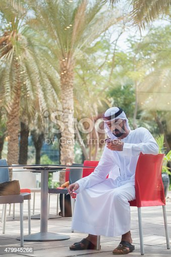 938436312 istock photo Traditionally Dressed Arab Businessman Texting on Cellphone at Outdoor Patio 479945266