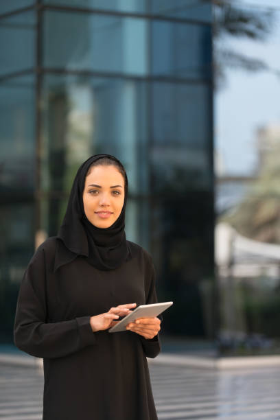 Traditionally Dressed Arab Businesswoman with Computer Tablet Outside Office Building stock photo