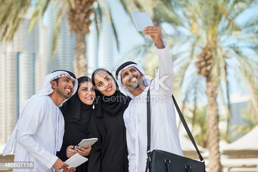 471250190istockphoto Traditionally Dressed Middle Eastern Businessman and Businesswomen Smiling for Selfie 480607116