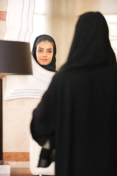 traditionell gekleideten nahöstlichen frau, die in großer gerahmter spiegel - badmöbel gäste wc stock-fotos und bilder