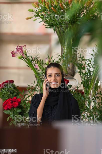 Traditionally dressed middle eastern woman with flowers talking on picture id471433540?b=1&k=6&m=471433540&s=612x612&h=hl1bj0m4ggkcmhxdcwif 5r ne8qofhrtxswlsytmxy=