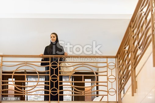 istock Traditionally Dressed, Smiling, Middle Eastern Woman Looking Down over Railing 472315614