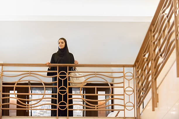 Traditionally Dressed, Smiling, Middle Eastern Woman Looking Down over Railing stock photo