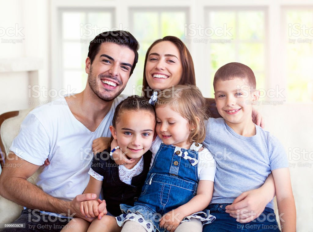 Traditionnal family portrait of five, sitting on couch at home. stock photo