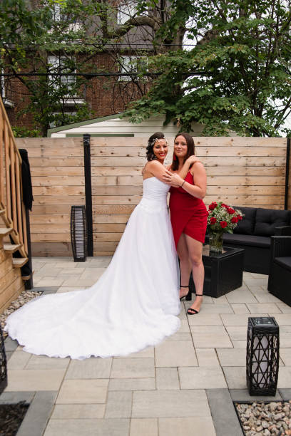 Traditionnal portrait of millenial bride with bridesmaid before wedding. stock photo