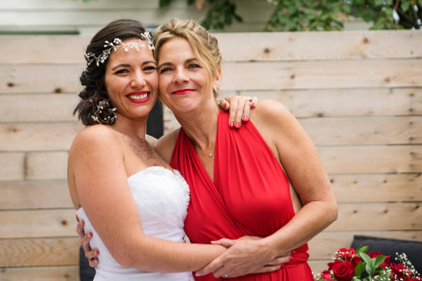 Traditionnal portrait of millenial bride with mother before wedding. stock photo