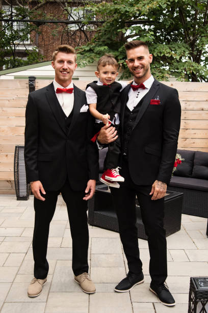 Traditionnal portrait of millenial groom with son and best man before wedding. stock photo