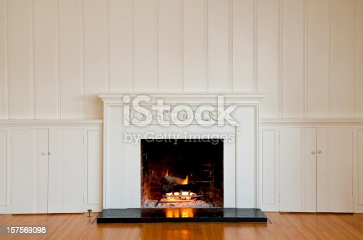 Traditional fireplace with floral relief moulding in empty domestic room.  There is a real roaring fire in the fireplace.
