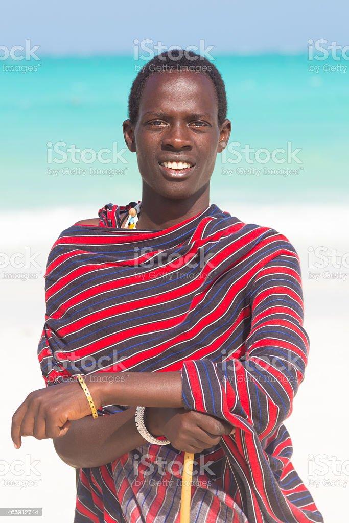 Traditonaly dressed black man on beach. stock photo