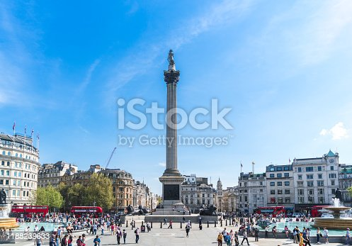 Trafalgar Square London UK on sunny Autumn afternoon, with a nutrally occuring crowd of dozens of people, walking, sightseeing or relaxing around the monument.