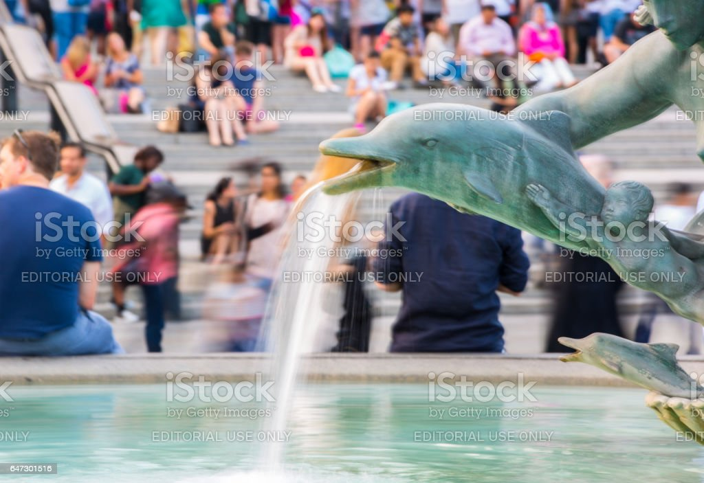 Trafalgar square with lots of people sitting on the stairs. Blurred image stock photo
