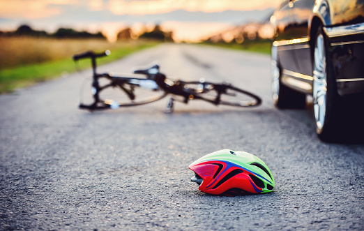 Traffic accident. Bicycle and helmet on the road after a car hit a cyclist