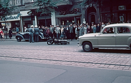 Berlin, Germany, 1959. A motorcyclist has an accident in Berlin traffic. The traffic police is on site. Inquisitive Berliners stand on the edge of the sidewalk and watch. Also: tenement houses, shops and cars.