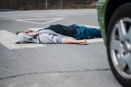 905971060 istock photo Traffic accident. Young man hit by a car 1057971514