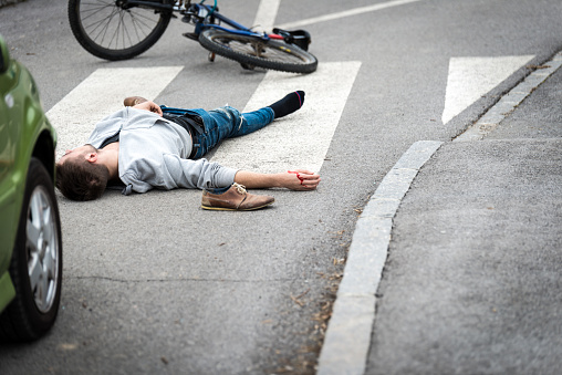 905971060 istock photo Traffic accident.Young man on bike hit by a car 654143658