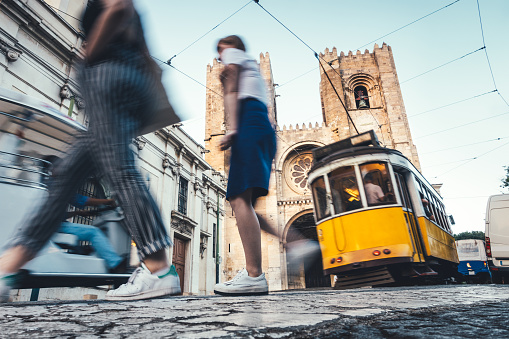 Traditional yellow tram driving on R. Augusto Rosa street towards Lisbon Cathedral. Tourists are crossing the street.