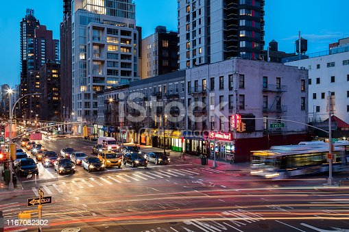 Car light trails from traffic flowing from Ed Koch Queensboro Bridge toward 2nd Ave and East 60th Street at night, Midtown Manhattan, New York City.