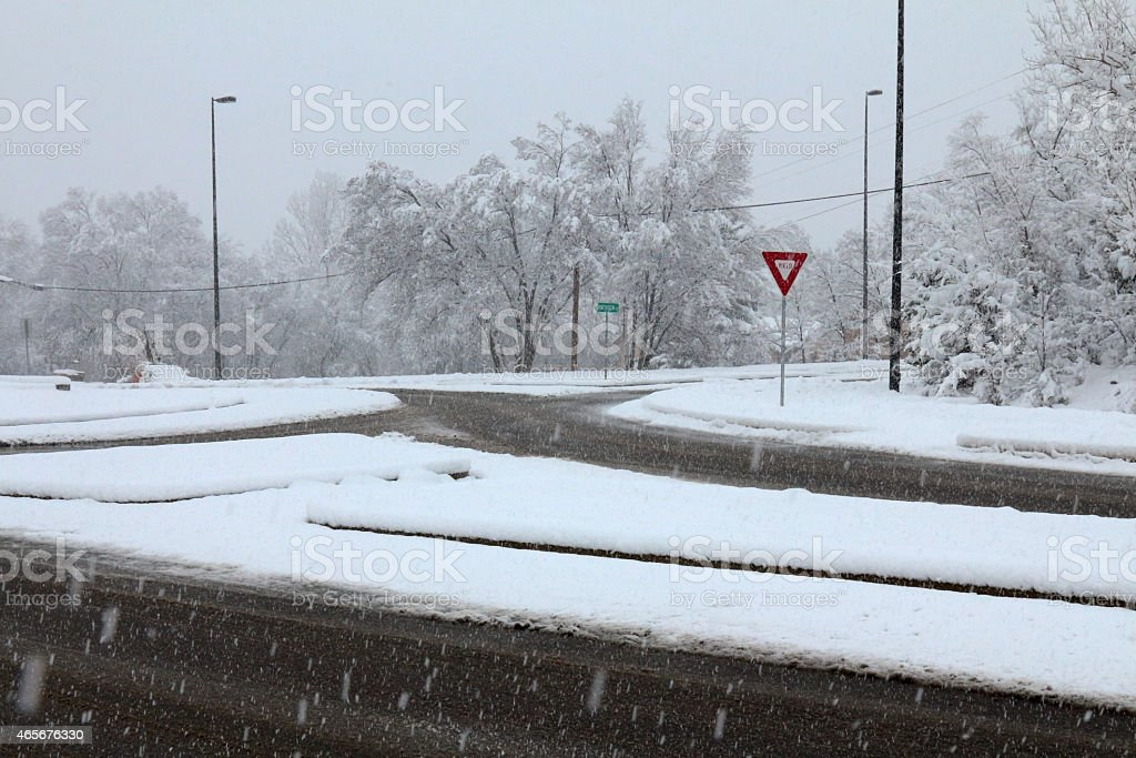 Traffic circle in a blizzard with a yield sign stock photo