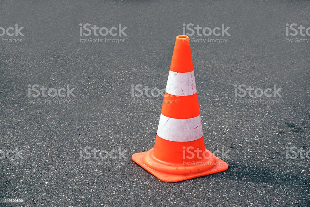 traffic cone, white and orange  on gray asphalt, copy space stock photo