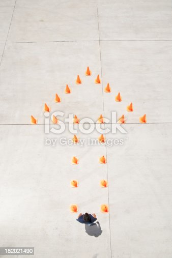 istock Traffic cones forming arrow with man at top 182021490