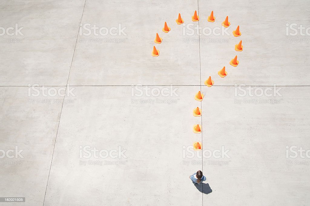 Traffic cones forming question mark with woman at point standing stock photo