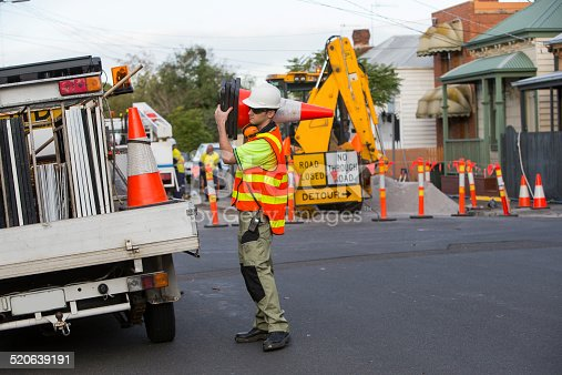 A young traffic controller worker in his twenties wearing dark safety glasses, a white hard hat and a high visibility orange vest is working on the side of the road packing large traffic orange cones back in the tray of a white utility truck. The road is closed with orange poles in front of an yellow excavator parked next to a pile of gravel. The day is overcast, the shy is white and there is no shadows. It is a suburban street with old weatherboard houses