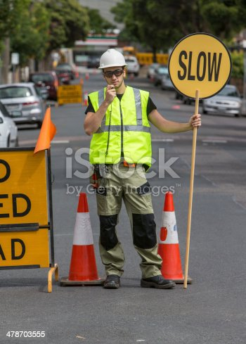 worker talking to radio and holding slow sign in the street, with traffic cones around him